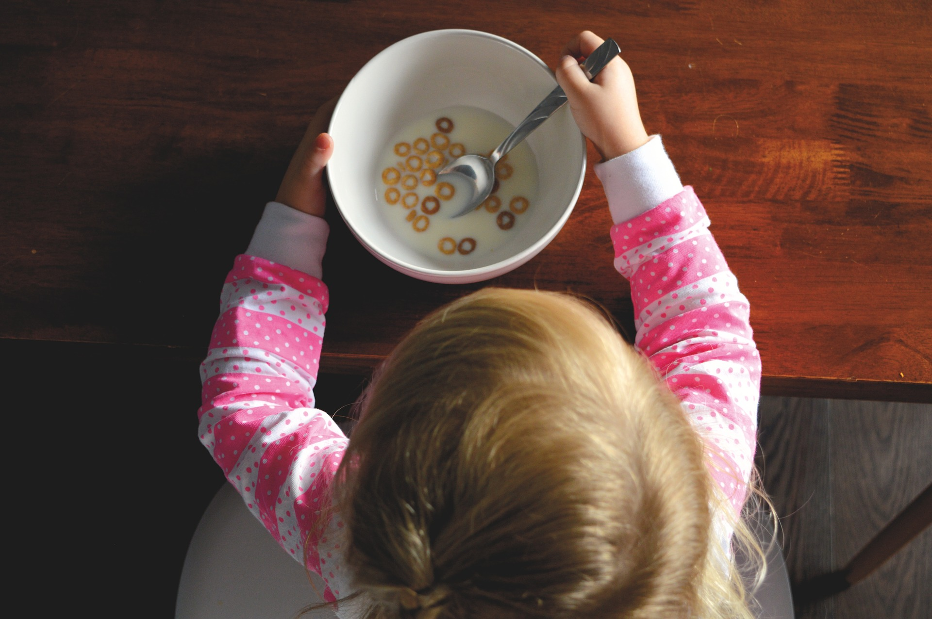 View from above of a toddler eating a bowl of cereal.